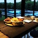 Le petit déjeuner en chambres d'hôtes face à la piscine miroir chauffée à débordement